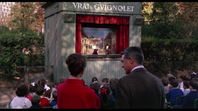 vídeos de stock, filmes e b-roll de 1963 excited children watch puppet show as cary grant, audrey hepburn and jacques marin stand at the back - marionete brinquedo