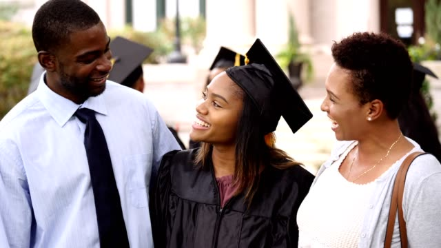 excited college graduate talks with parents after graduation ceremony - graduation stock videos & royalty-free footage