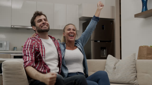 vídeos de stock e filmes b-roll de excited couple watching a football match on tv celebrating - sitting