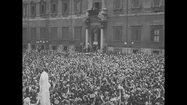 ms excited crowd cheers waves outside the quirinal palace in rome / ws crowd with king victor emmanuel iii and prince paul of rome in extreme far... - 旧ユーゴスラビア点の映像素材/bロール