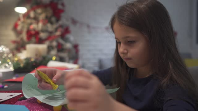excited cute girl making and decorating a new year greeting card while enjoying a holiday spirit - new year card stock videos & royalty-free footage