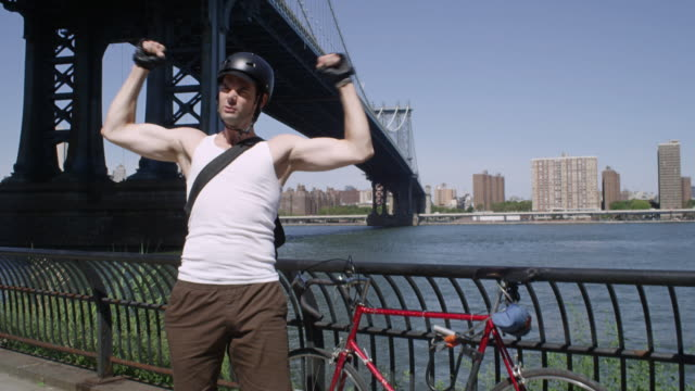 Excited cyclist cheering in front of Manhattan Bridge
