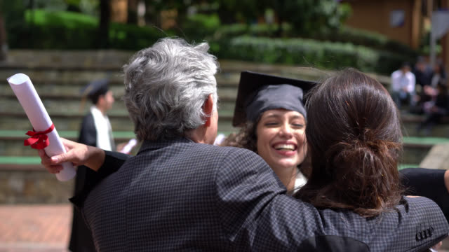 excited daughter running to celebrate and hug her parents after receiving her degree at colllege - diploma stock videos & royalty-free footage