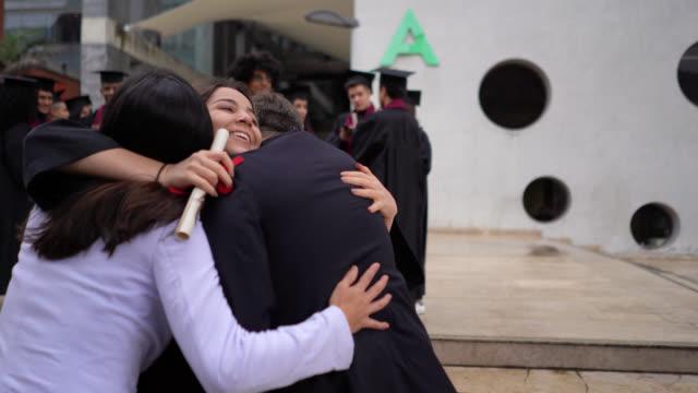 stockvideo's en b-roll-footage met opgewekte dochter die naar haar ouders na het ontvangen van haar universitaire diploma loopt dat hen allen koestert die gelukkig kijken - slagen school