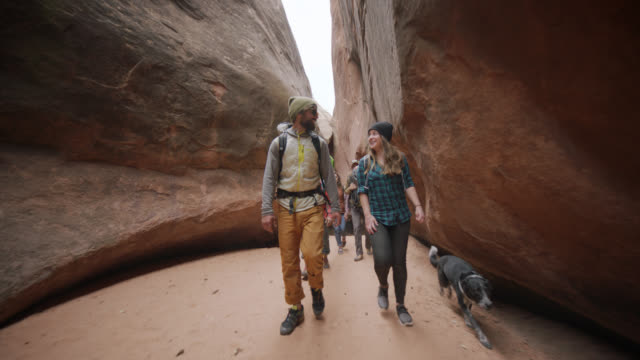 SLO MO. Excited dog runs ahead as group of friends walk and talk through slot canyon on Moab adventure.