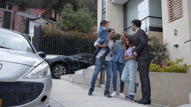 excited family receiving their car at home after purchasing it online and salesman hands them the keys - salesman stock videos & royalty-free footage