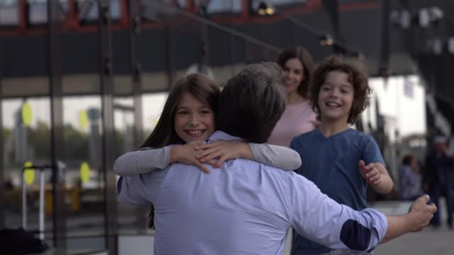 vídeos y material grabado en eventos de stock de familia emocionada corriendo hacia papá para abrazarlo en las llegadas del aeropuerto - arrival
