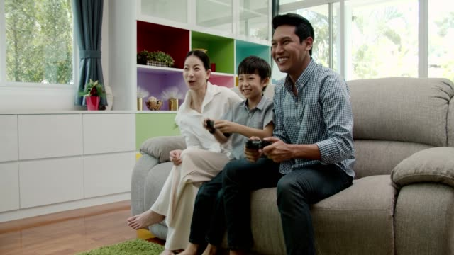 excited father and son pressing console buttons while playing video game at home - handheld video game stock videos & royalty-free footage