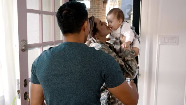 excited female soldier is warmly greeted by family - husband stock videos & royalty-free footage