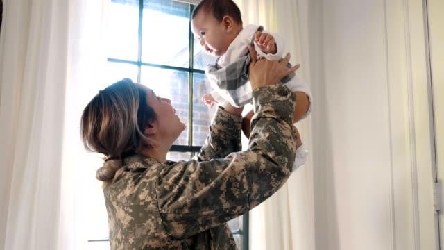 la soldato donna eccitata torna a casa dalla sua bambina - forze armate video stock e b–roll