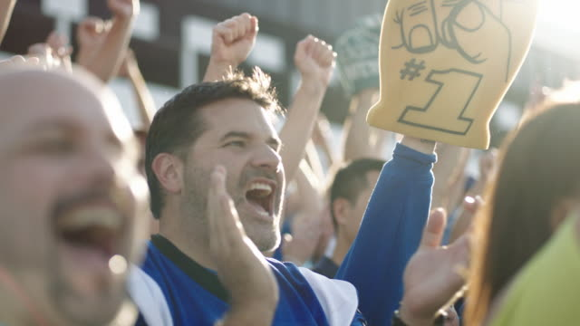 slo mo. excited football fans clap and cheer in crowded stadium. - football点の映像素材/bロール