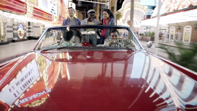 Excited friends cruising through downtown Las Vegas in classic convertible throw hands in the air and cheer