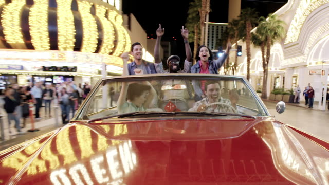 excited friends cruising through downtown las vegas in classic convertible throw hands in the air and cheer - excess stock videos & royalty-free footage