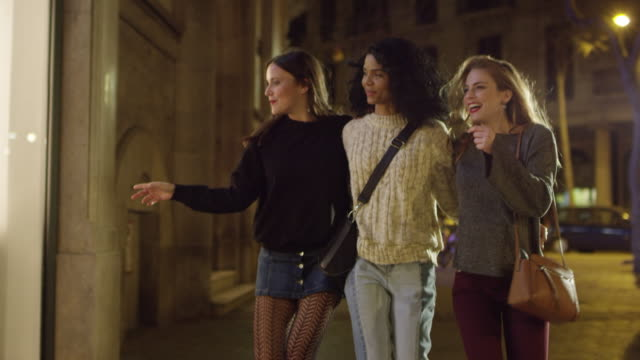 excited friends doing window shopping at night - punto di vista frontale video stock e b–roll