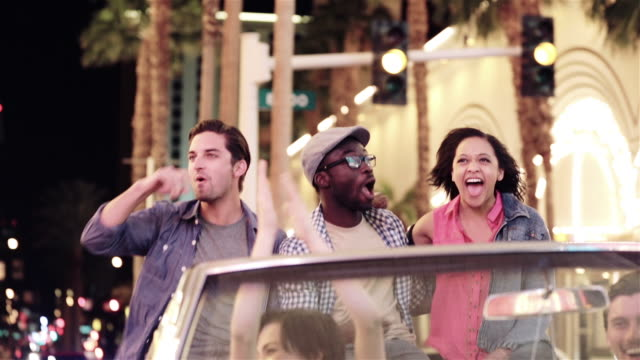 Excited friends ride on backseat of classic convertible through downtown Las Vegas