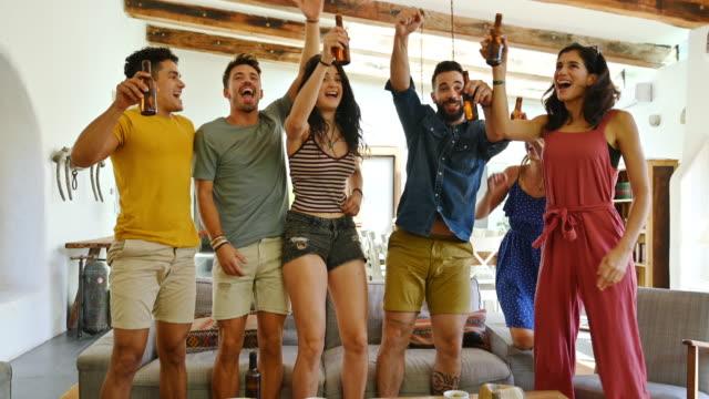 vídeos y material grabado en eventos de stock de amigos emocionados de pie y animando al equipo deportivo en la televisión - de origen español o portugués
