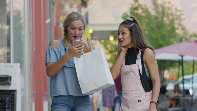 excited girl carrying shopping bag relaxing then answering phone / provo, utah, united states - teenage girls stock videos & royalty-free footage