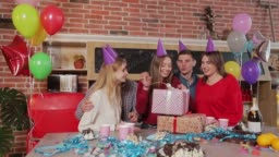 Excited girl, surrounded by sincere friends, opening birthday presents, young beautiful brunette sitting on big couch among smiling guests