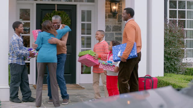 Excited grandfather hurries outside to welcome and hug family for Christmas (dolly-shot)