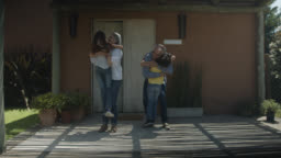 Excited grandkids running to hug their loving grandparents while they stand at the entrance of their home