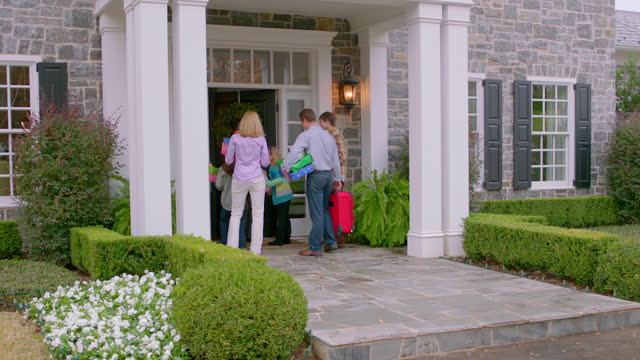 Excited grandmother greets arriving family at the door (dolly-shot)