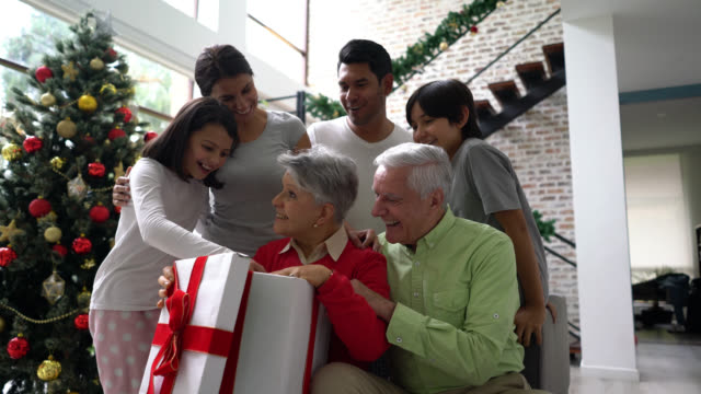 excited grandmother opening a big christmas present while loving family is around her smiling - christmas gift stock videos & royalty-free footage