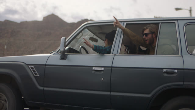 Excited group of friends cheer and wave hands out car window on Moab road trip.