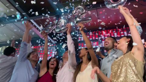 stockvideo's en b-roll-footage met opgewonden groep vrienden die aftellen tot middernacht op een nieuwjaarsfeest in een bar - nachtclub