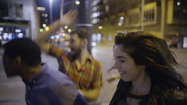 Excited group of friends cross street in downtown Austin, Texas at night