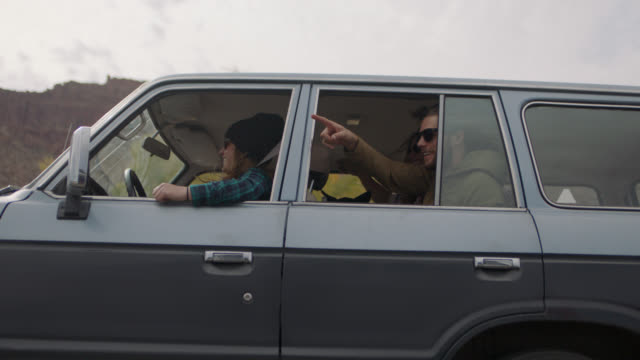 vidéos et rushes de slo mo. excited group of friends smile and point out car window on moab road trip. - car point of view