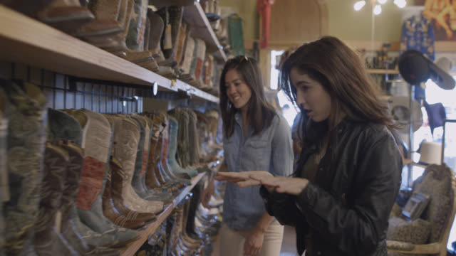 excited group of friends walk through western store looking at cowboy boots - ブーツ点の映像素材/bロール