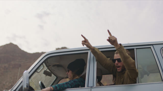 SLO MO. Excited group of friends wave hands out car window and cheer as they pass on Moab road trip.
