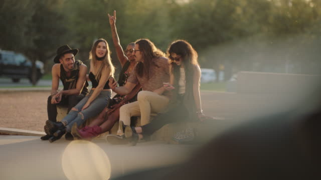 excited group of hipster friends look at smartphone while sitting on city street corner waiting for ride to music festival. - waiting stock videos & royalty-free footage