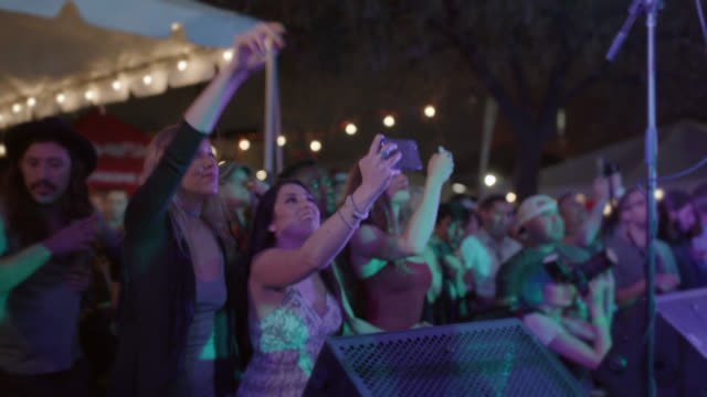 excited group of millennial hipsters dance and record the concert with their cell phones at a popular music festival - beatnik stock videos & royalty-free footage