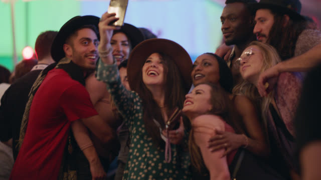 excited group of millennial hipsters take a group selfie with a bohemian woman's iphone at a popular music festival - selfie video stock e b–roll