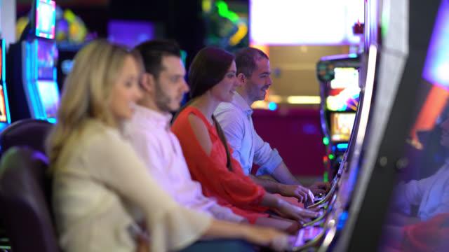 vídeos y material grabado en eventos de stock de entusiasmado grupo de personas jugando en las máquinas tragaperras en el casino - máquina con ranura