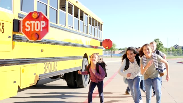 vídeos de stock e filmes b-roll de excited group of students run after getting off of school bus - marca de estrada