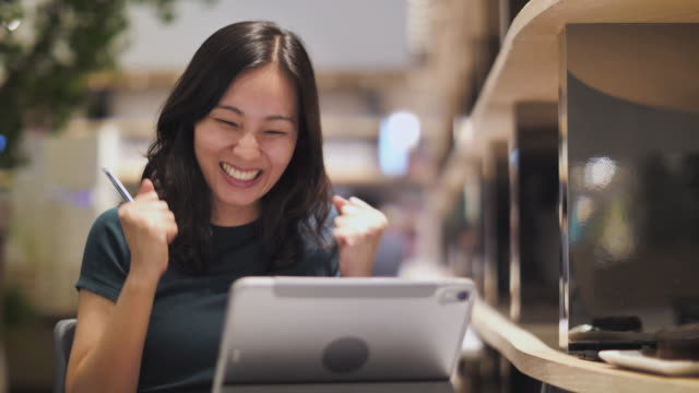 excited happy asian woman looking at digital tablet excited expressing winning gesture - punching the air stock videos & royalty-free footage