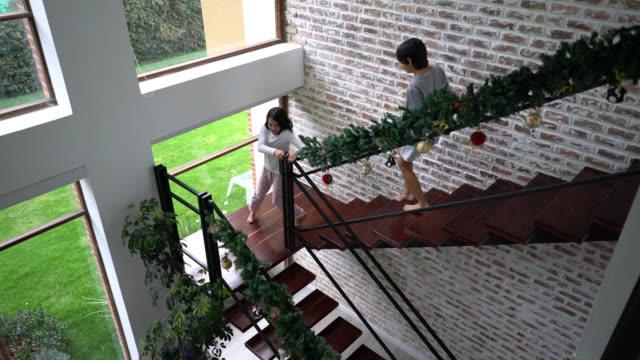 aufgeregte kinder laufen am weihnachtsmorgen die treppe hinunter ins wohnzimmer, wo eltern und großeltern auf sie warten - draufsicht stock-videos und b-roll-filmmaterial
