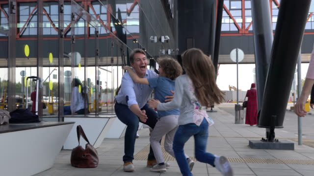 excited kids running to hug their dad at the entrance of the airport with mom - embracing stock videos & royalty-free footage