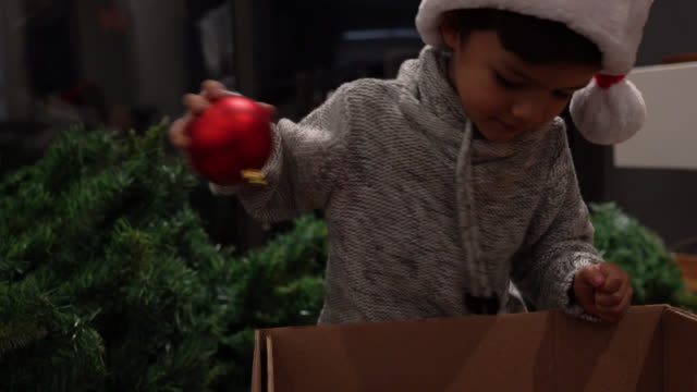 excited little boy taking out christmas decorations from the box - decorating the christmas tree stock videos & royalty-free footage
