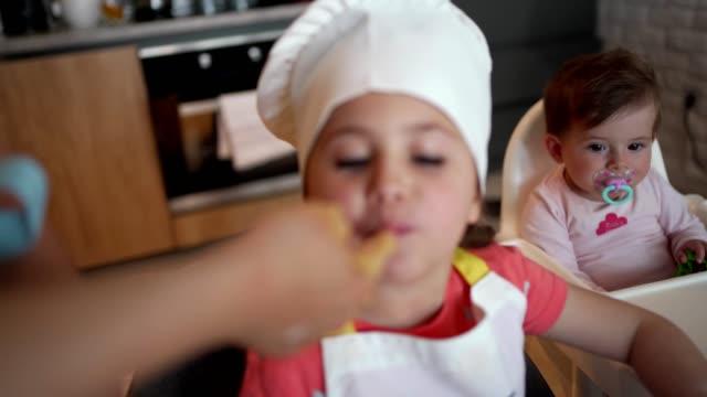 vídeos y material grabado en eventos de stock de emocionada pequeña mezcla de degustación de chef hecha por ella para el pastel - saborear
