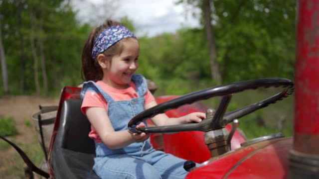 excited little girl enjoying her adventure at family ranch and pretending to drive a tractor - tractor stock videos & royalty-free footage