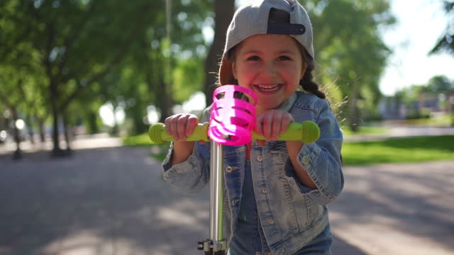 excited little girl enjoying sunny day while having fun on a push scooter - 4 5 years stock videos & royalty-free footage