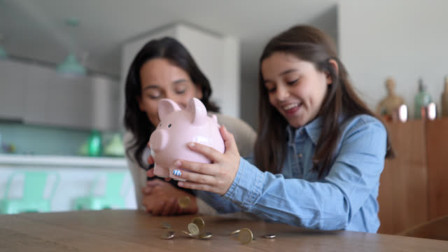 excited little girl opening her piggybank to count her savings and mom very excited clapping and smiling - economia familiare video stock e b–roll