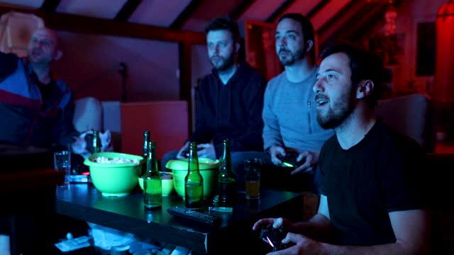 vídeos de stock, filmes e b-roll de amigos homens animados tendo uma noite divertida, enquanto jogam videogame na caverna do homem - amizade masculina