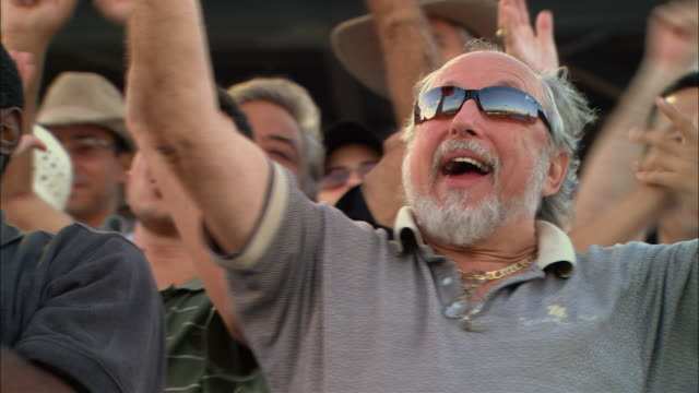 stockvideo's en b-roll-footage met la cu excited man cheering and waving among diverse crowd in bleachers / homestead, fl, usa - juichen