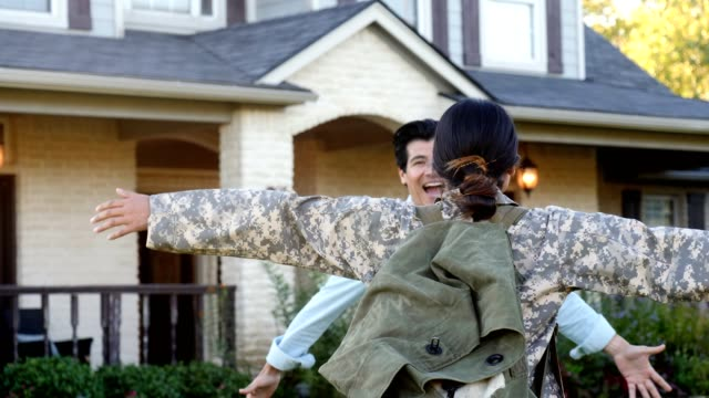 vídeos de stock e filmes b-roll de excited man greets wife after long military deployment - regresso ao lar