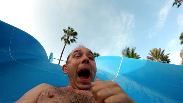 excited man on the water slide in the water park in slow motion - water slide stock videos & royalty-free footage