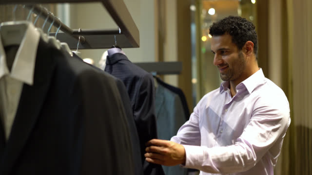 Excited man smiling because he found a suit he likes trying it on over him while looking at mirror
